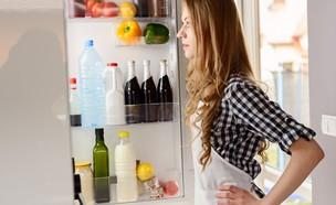 אישה מול מקרר פתוח (צילום: plantic, Shutterstock)