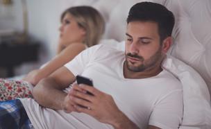 גבר מסתכל בסמארטפון במיטה (אילוסטרציה: kateafter | Shutterstock.com )