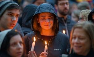 תושבים מדליקים נרות לזכר הנרצחים (צילום: רויטרס, חדשות)
