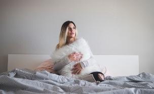 מחזיקה כרית על המיטה (צילום: victor-hughes-on-unsplash)