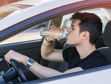 איש שותה תוך כדי נהיגה (צילום: ArtOfPhotos, shutterstock)