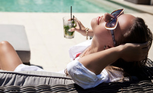 אישה עשירה יושבת על ספרה עם מוחיטו (אילוסטרציה: kateafter | Shutterstock.com )
