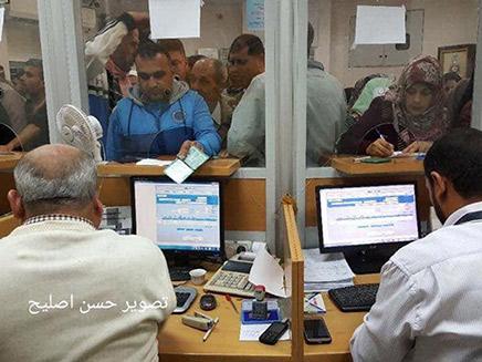 פלסטינים עומדים בתור לקבל כסף בעזה