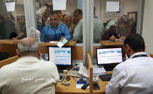 פלסטינים עומדים בתור לקבל כסף בעזה (צילום: חדשות)