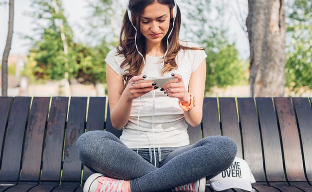 אישה צעירה בטלפון (צילום:  kikovic, shutterstock)