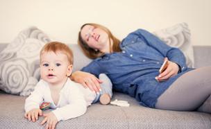 תינוק משחק בזמן שאמו ישנה מאחוריו (אילוסטרציה: kateafter | Shutterstock.com )