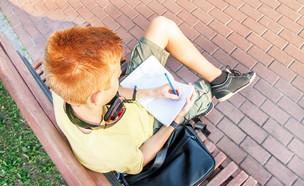 ילד יושב על ספסל וכותב במחברת (אילוסטרציה: By Dafna A.meron, shutterstock)