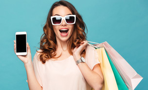 אישה מחזיקה שקיות קניות וסמארטפון (צילום:  Dean Drobot, ShutterStock)