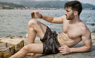 גבר מצלם סלפי על החוף (צילום: Shooting Star Studio, Shutterstock)
