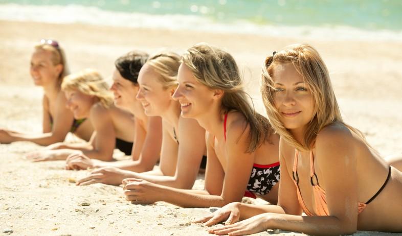 בנות משתזפות על חוף הים (צילום: Wallenrock, Shutterstock)