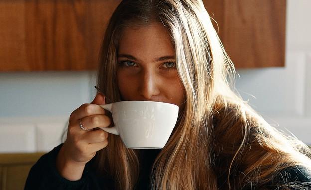 אישה צעירה שותה קפה (צילום:  Gian Cescon on Unsplash)