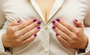 אישה מניחה ידיים על החזה (צילום:  Bacho, shutterstock)
