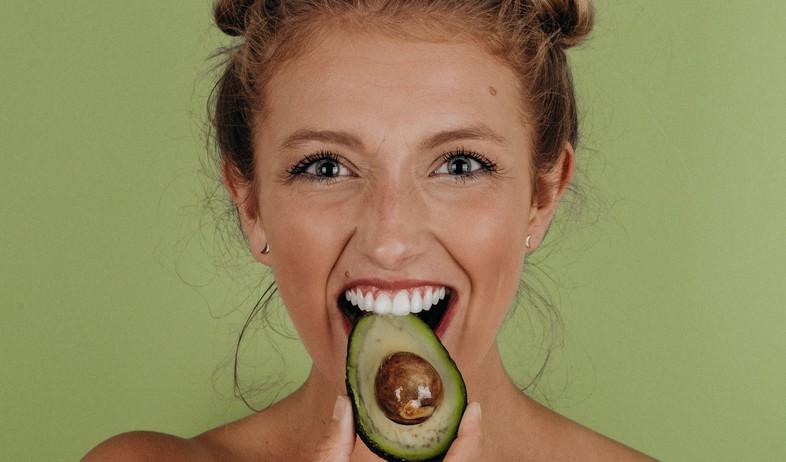 אישה אוכלת אבוקדו (צילום: noah-buscher-unsplash)