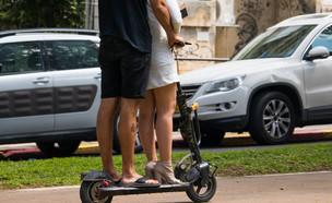 זוג רוכב על קורקינט חשמלי בשדרות רוטשילד בתל אביב (צילום: By Dafna A.meron, shutterstock)