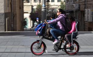אמא ושני ילדים רוכבים על אופניים חשמליים בירושלים (צילום: kateafter | Shutterstock.com )