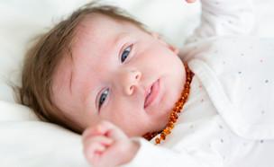 תינוק עם שרשרת ענברים (צילום:  epiximages, shutterstock)