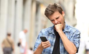 גבר כועס קורא סמס (אילוסטרציה: Shutterstock)