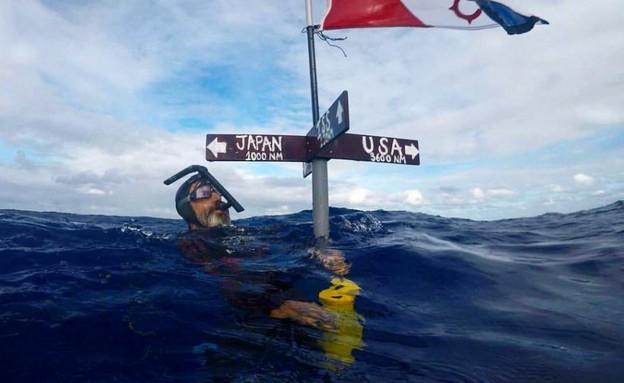 """בן לקומטה ליד מצוף שמסמן את המרחק בין יפן לארה""""ב (צילום: בן לקומטה וצוות Seeker)"""