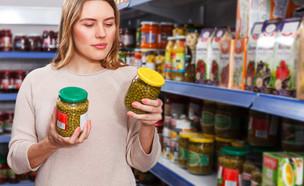 אישה בודקת צנצנות חמוצים בסופרמרקט (אילוסטרציה: kateafter | Shutterstock.com )