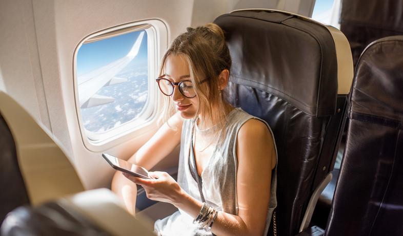 אישה יושבת ליד החלון בטיסה (צילום:  RossHelen, shutterstock)