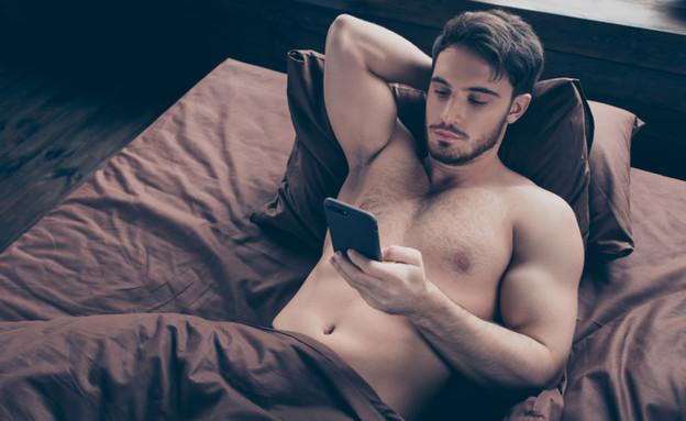 גבר מסמס במיטה (צילום: Roman Samborskyi, shutterstock)