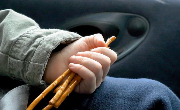 ילד אוכל באוטו (צילום: shutterstock By Jevanto Productions)