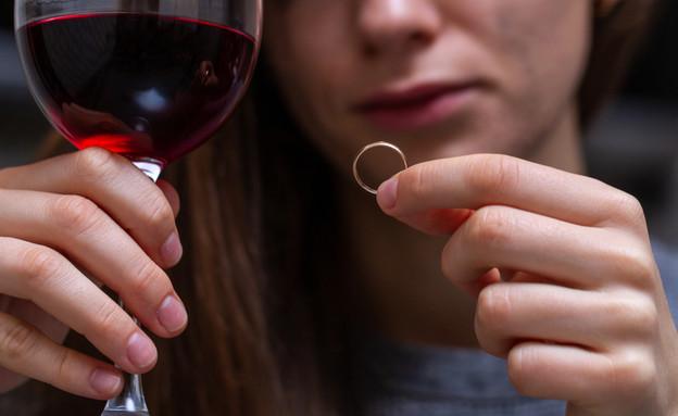 גרושה מסתכלת על טבעת נישואים (אילוסטרציה: kateafter | Shutterstock.com )