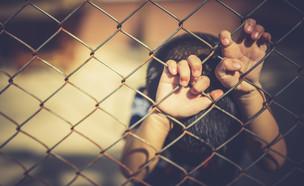 ילד מחזיק בגדר של בית ספר (אילוסטרציה: kateafter | Shutterstock.com )