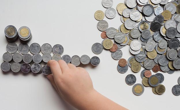 יד של ילד משחקת במטבעות (אילוסטרציה: By Dafna A.meron, shutterstock)