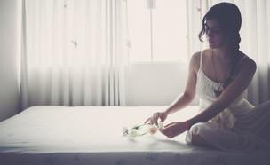 אישה יושבת על מיטה עם זר לבן (אילוסטרציה: unsplash)