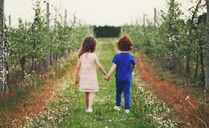 ילד וילדה מטיילים במטע פורח (אילוסטרציה: kateafter | Shutterstock.com )