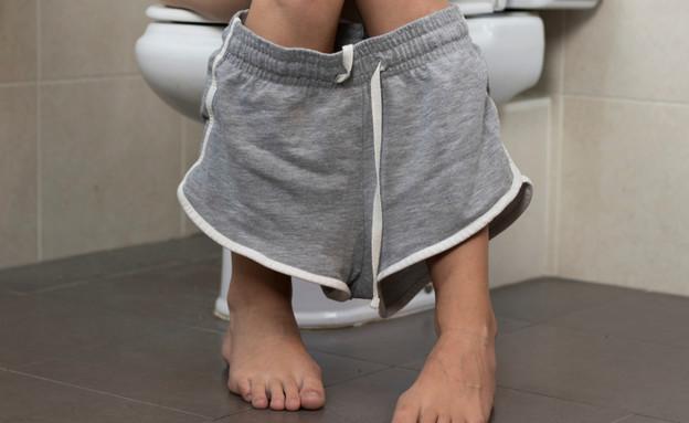 אישה יושבת על אסלה בשירותים (צילום:  SircPhoto, shutterstock)