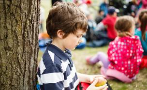 ילד יושב לבד ליד עץ (צילום: By Dafna A.meron, shutterstock)