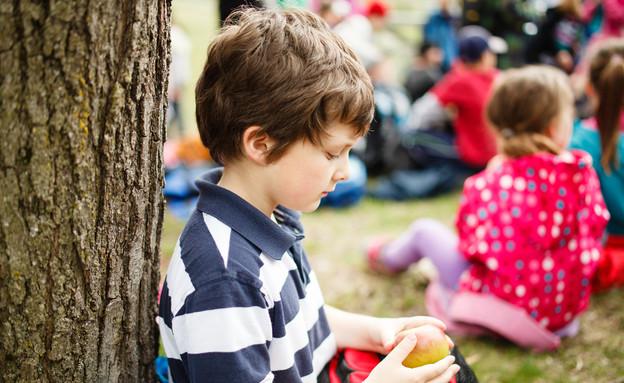 ילד יושב לבד ליד עץ (צילום: kateafter | Shutterstock.com )