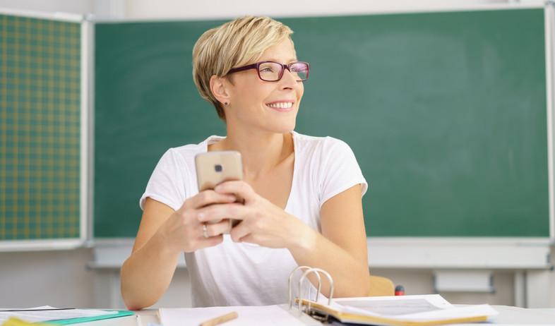 מורה מחזיקה טלפון סלולרי בכיתה (אילוסטרציה: kateafter   Shutterstock.com )
