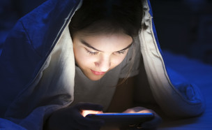 ילדה מתחת לשמיכה עם טלפון סלולרי (אילוסטרציה: By Dafna A.meron, shutterstock)