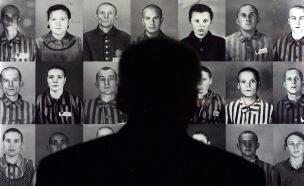 איש מתבונן בתמונות של נספים בשואה (צילום: רויטרס, חדשות)