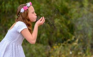 ילדה עם זר פרחים בשדה (אילוסטרציה: By Dafna A.meron, shutterstock)