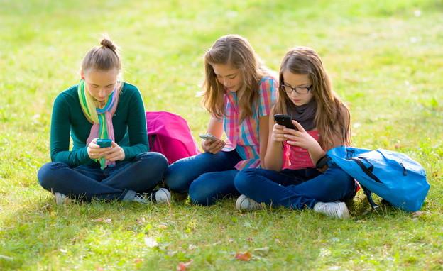 ילדות יושבות על דשא עם סמארטפון (צילום: By Dafna A.meron)