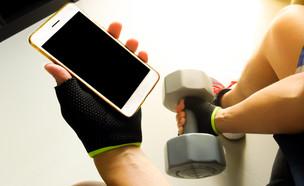 משתמש בסמארטפון בחדר כושר (צילום: Natural Mosart, ShutterStock)