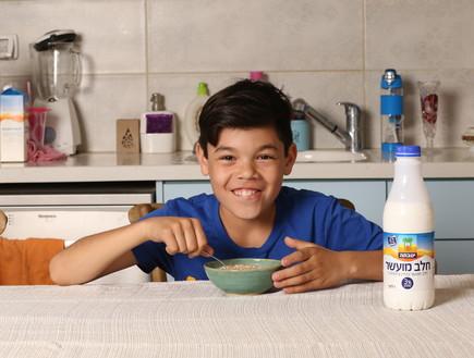 ילד אוכל דגני בוקר עם חלב