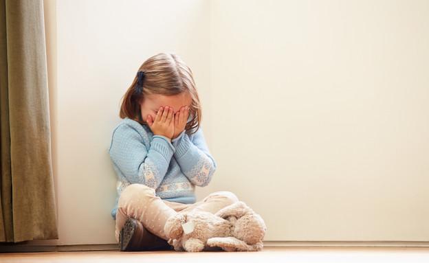 ילדה עצובה יושבת בפינה