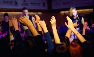 פאב צפוף - אנשים מנופפים ביד (צילום: Olesia Bilkei, ShutterStock)
