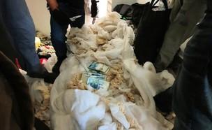 המזומן שנתפס בתוך כלי המיטה בבית (צילום: דוברות המשטרה)