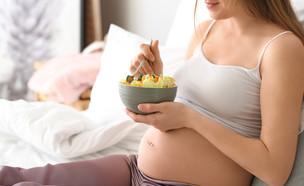 אישה בהיריון אוכלת סלט פירות במיטה (אילוסטרציה: Pixel-Shot, shutterstock)