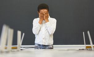 תלמיד עומד בפני כיתה ריקה ומסתיר את פניו בידיו (אילוסטרציה: shutterstock)