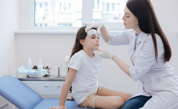 רופאה בודקת את ראשה של ילדה (אילוסטרציה: YAKOBCHUK VIACHESLAV, shutterstock)
