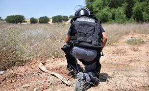 חבלן משטרתי בזירת נפילת רקטה בעוטף עזה (צילום: דוברות המועצה האזורית חוף אשקלון)