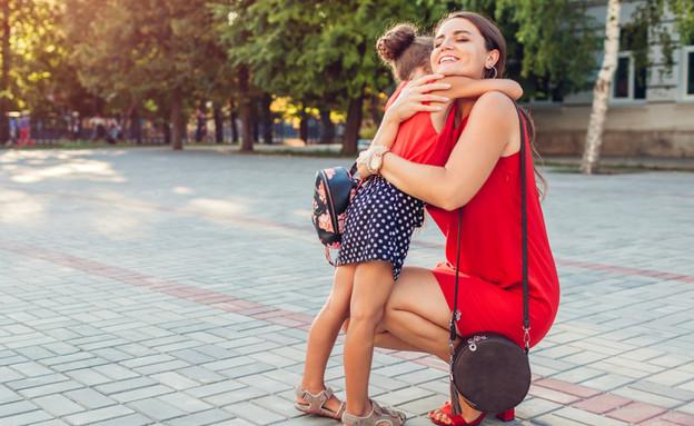 אמא מחבקת את בתה אחרי בית ספר