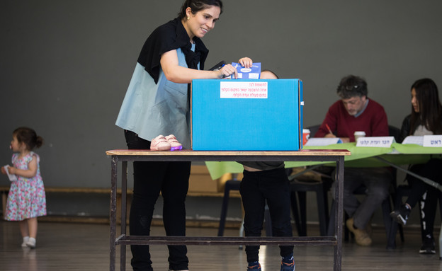אישה וילד מצביעים בקלפי (צילום: פלאש 90)